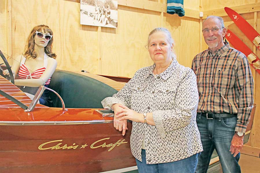 Bruce Misinski, president of the Lake County Historical Society, and Jill Engelman, museum curator, stand beside a 1949 Chris Craft boat, a regal vessel from Lake County's rich waterway history.