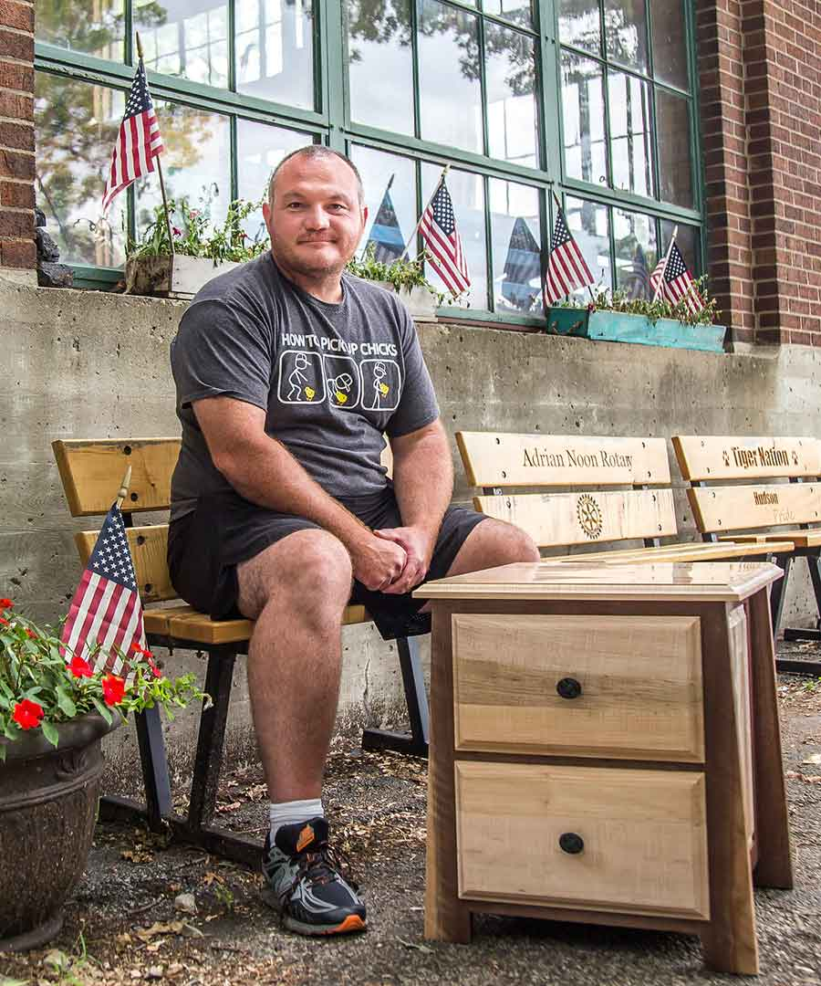 U.S. Army veteran Chad Diffin sits outside of the woodshop next to his most recent project, a two-toned nightstand.